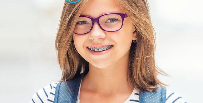 Frase: um novo ano letivo, novos momentos para sorrir. menina a sorrir com aparelho dentário.
