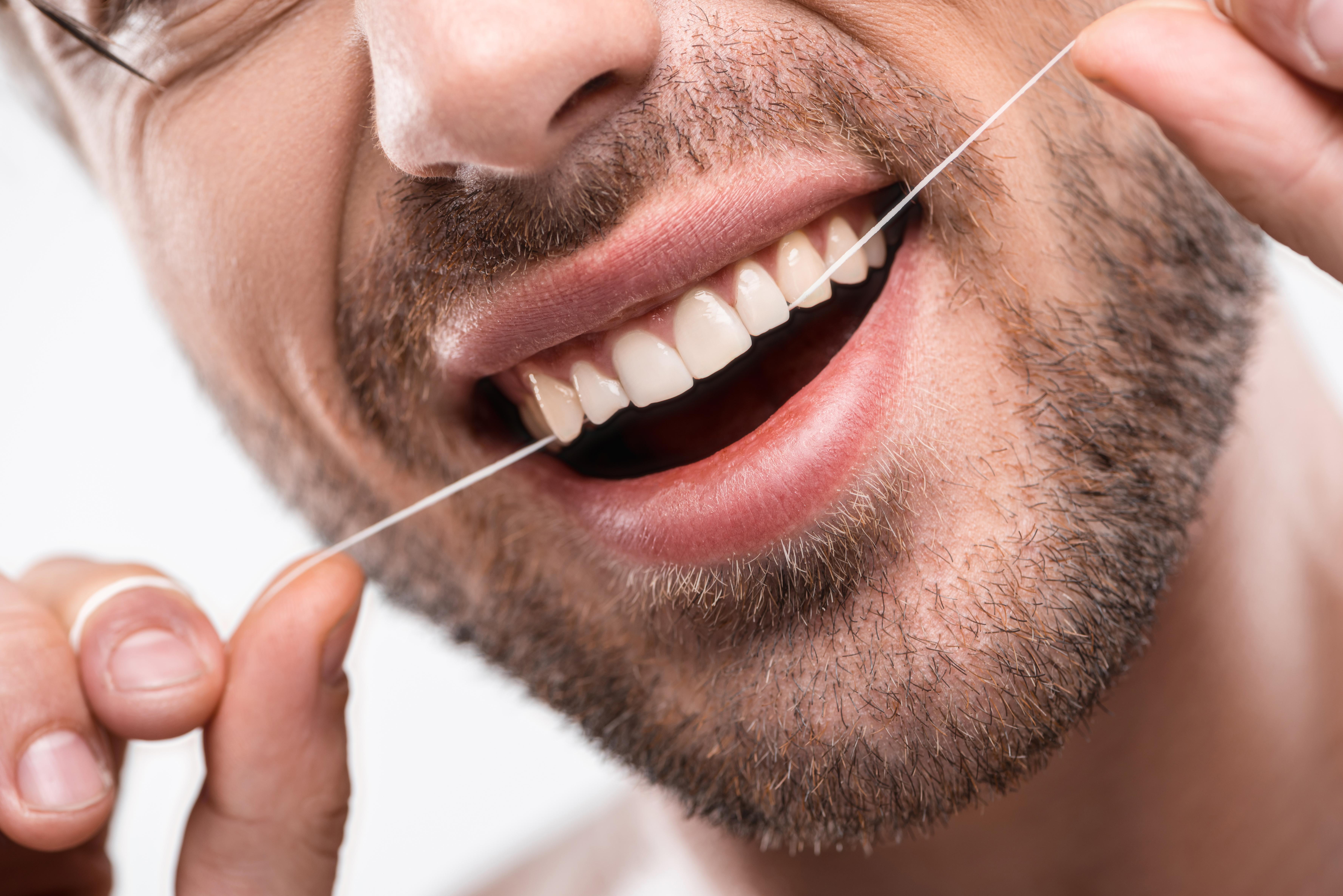 c9c8c280d A importância de usar fio dental. Homem a passar fio dental nos dentes